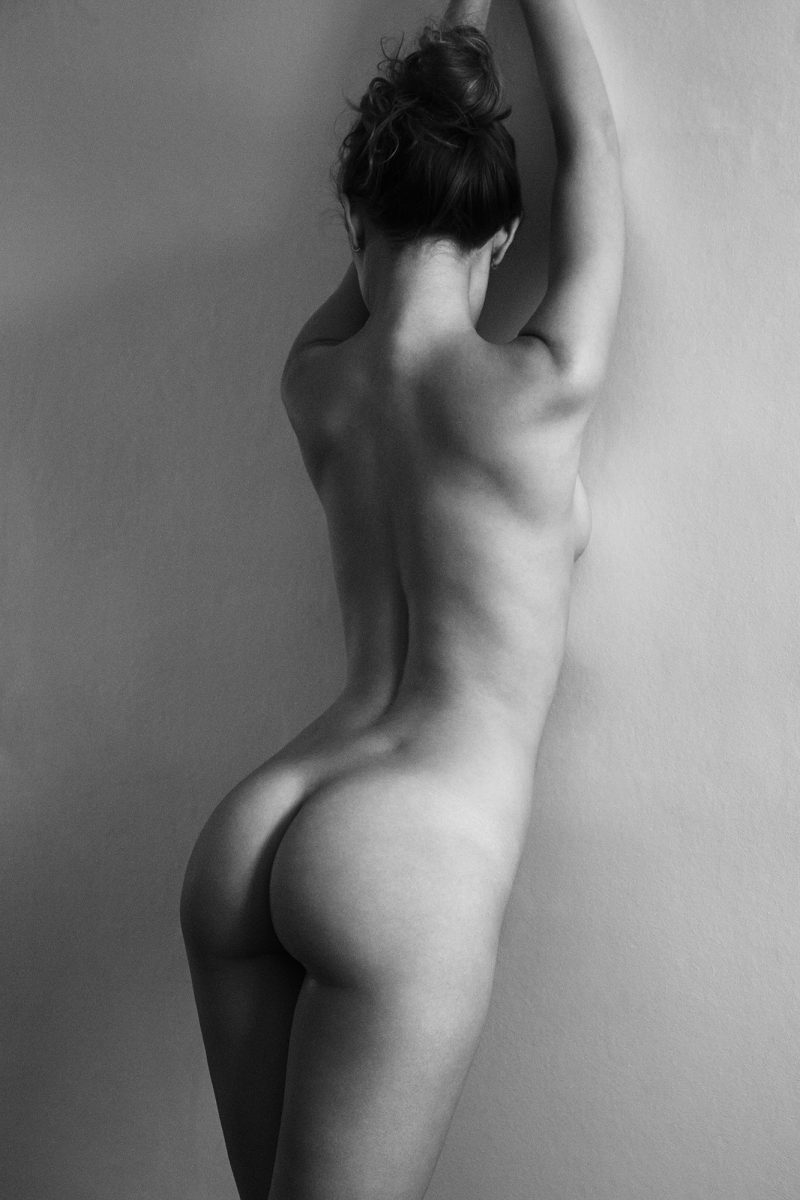 Naked girl from the back leaning against a wall by Stefan Rappo