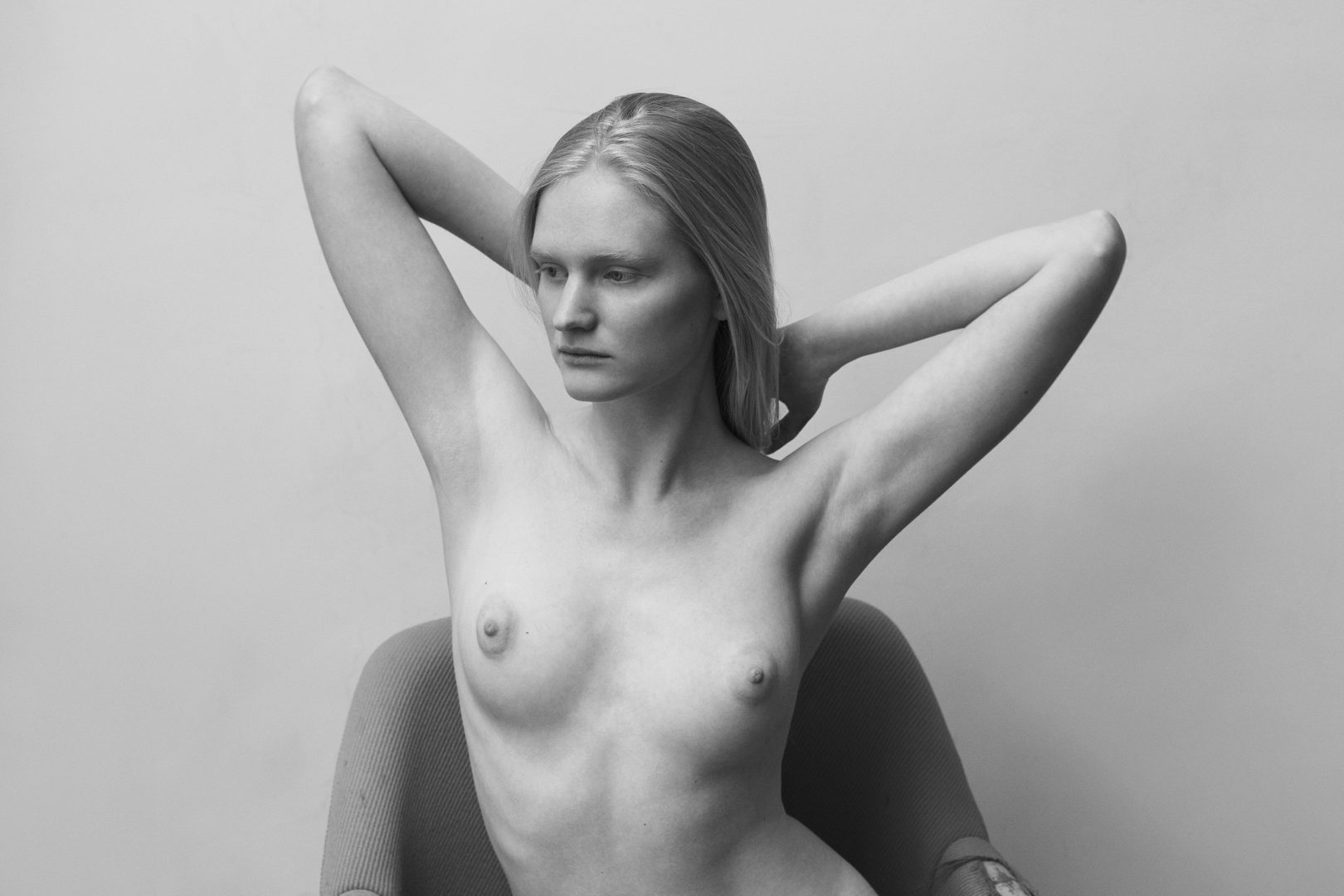 Portrait of naked girl sitting on chair by Stefan Rappo