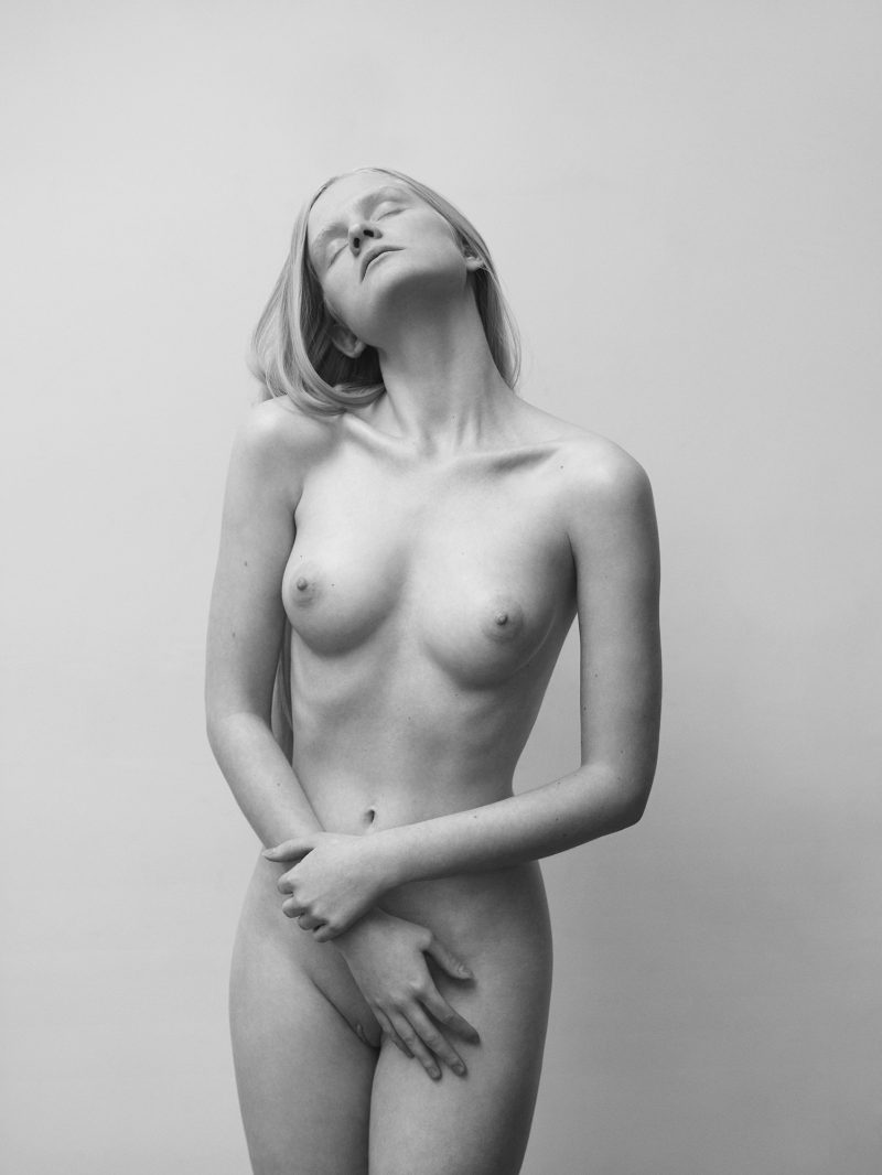 Naked girl in front of a wall by Stefan Rappo