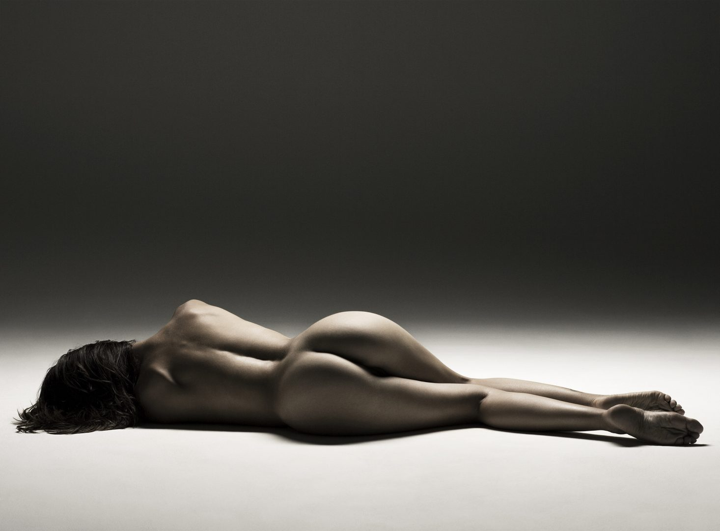 Naked girl from the back lying on floor by Stefan Rappo