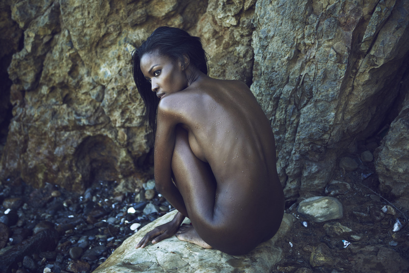 Naked girl on beach in front of big rock by Stefan Rappo