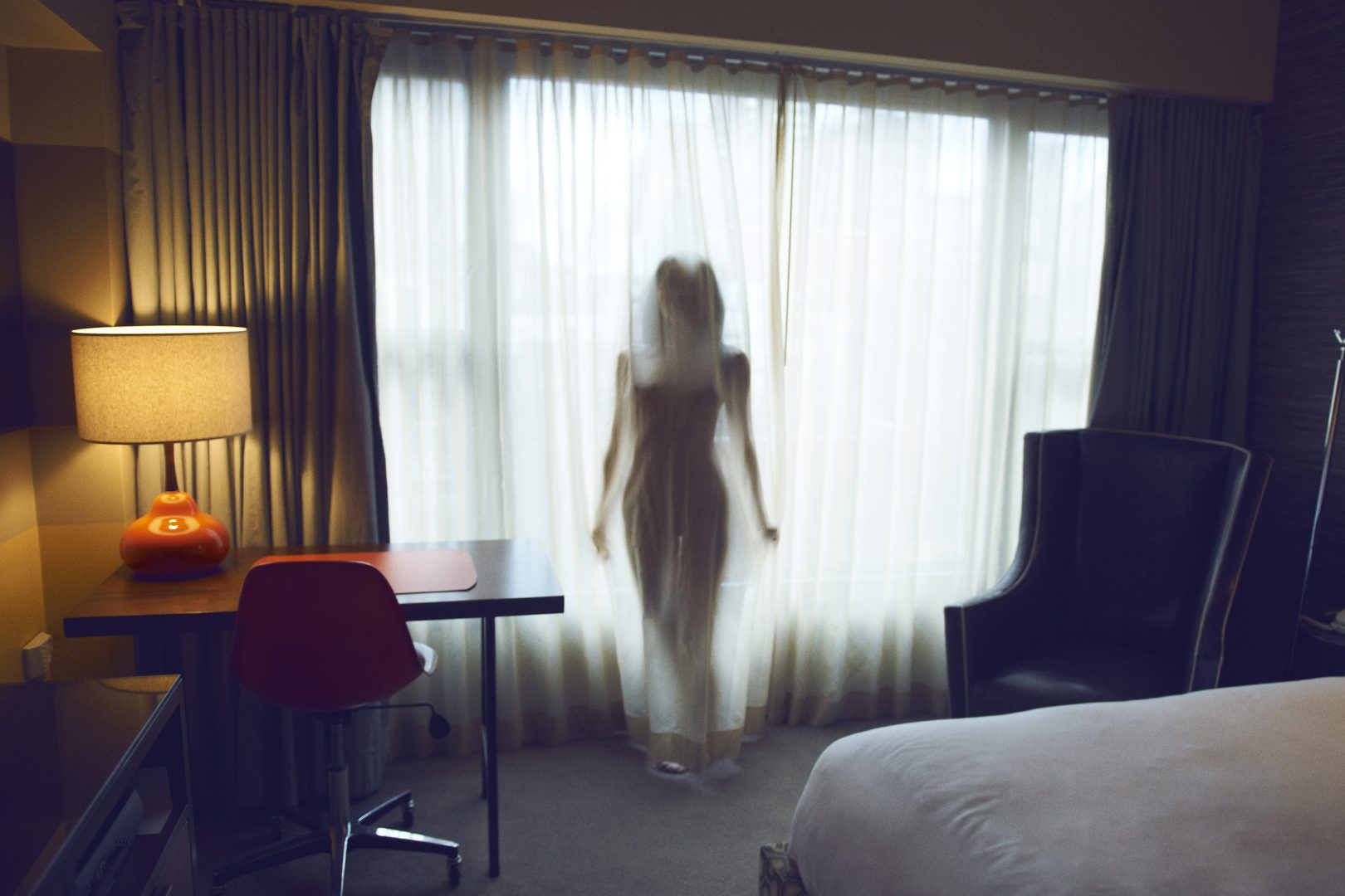 Naked girl behind a curtain in hotel room by Stefan Rappo