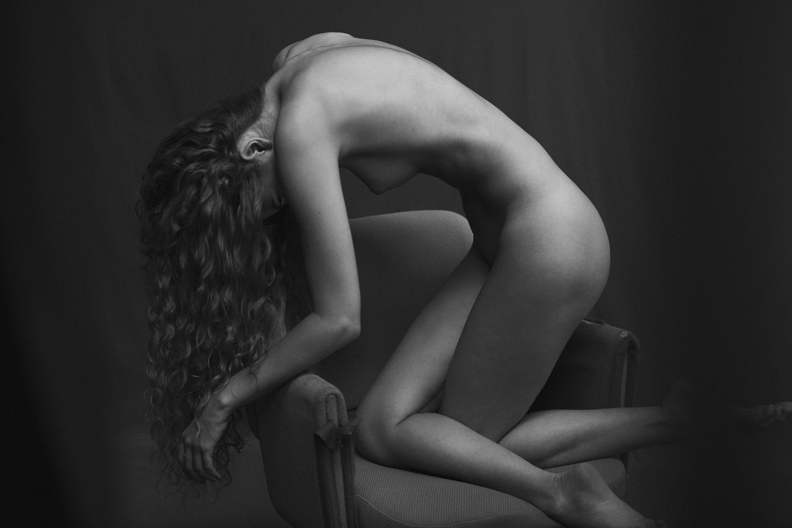 Naked girl from the side kneeing on chair by Stefan Rappo