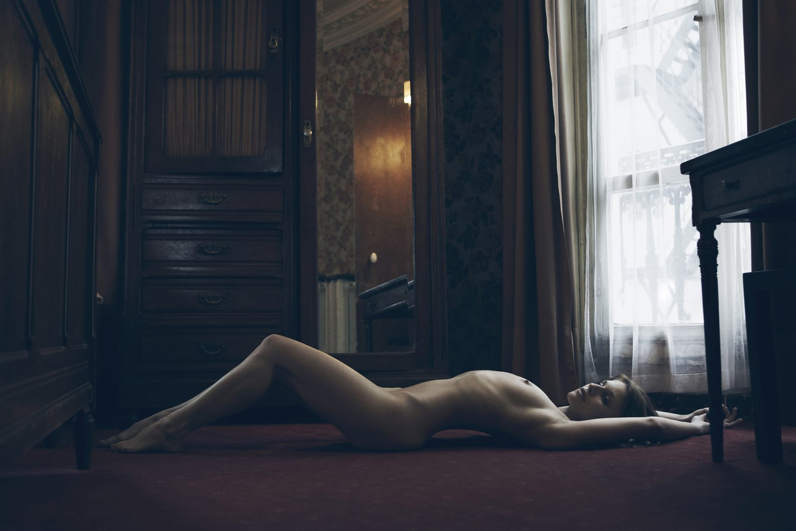Naked girl lying on floor in hotel room by Stefan Rappo