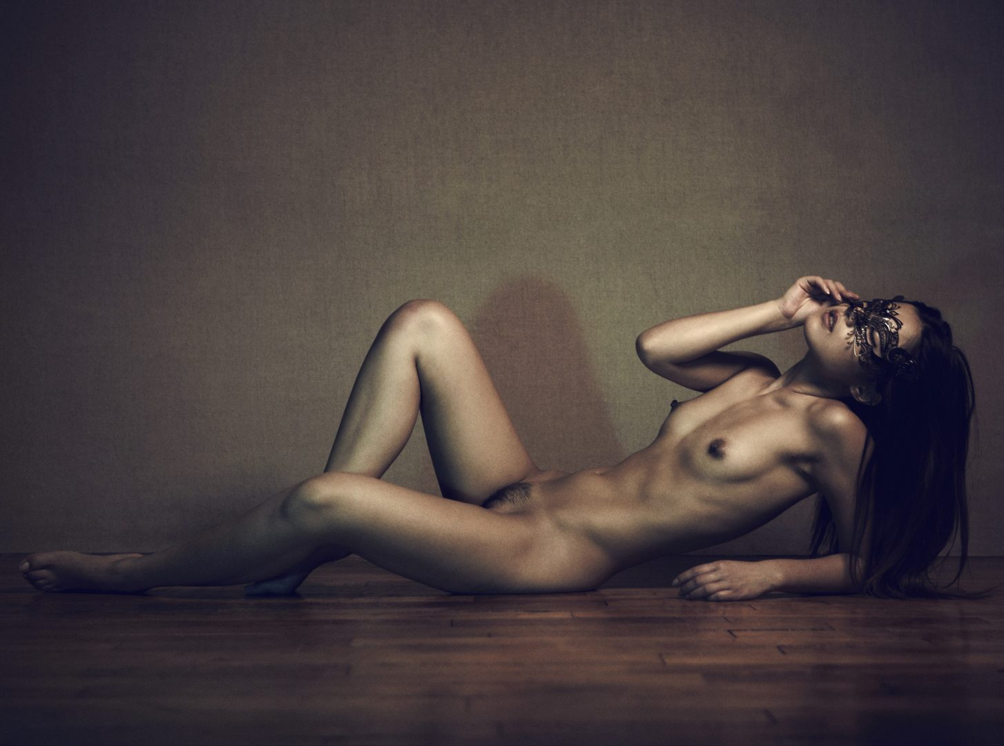Naked girl with mask lying on floor by Stefan Rappo