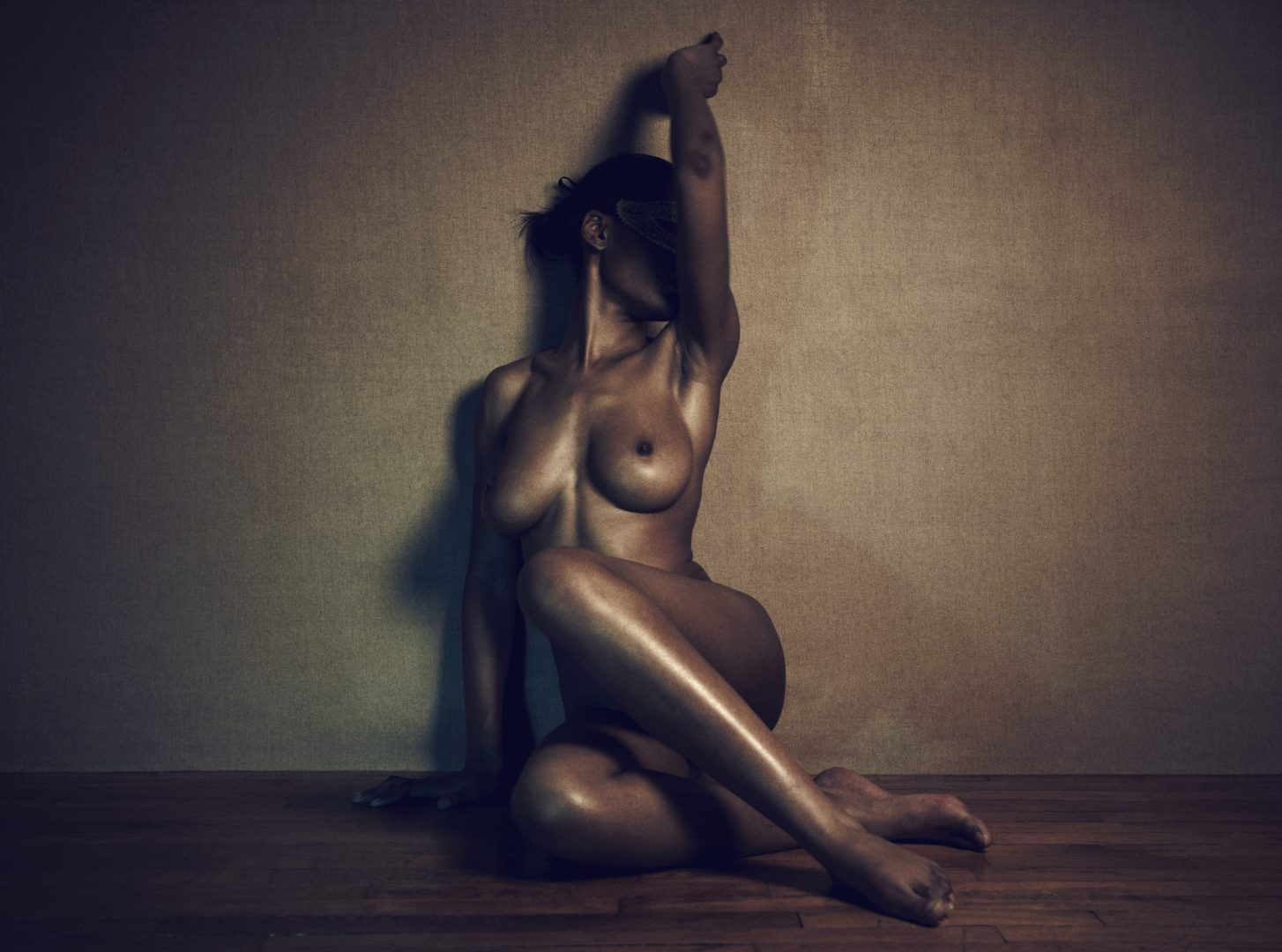 Naked girl with mask sitting on floor by Stefan Rappo