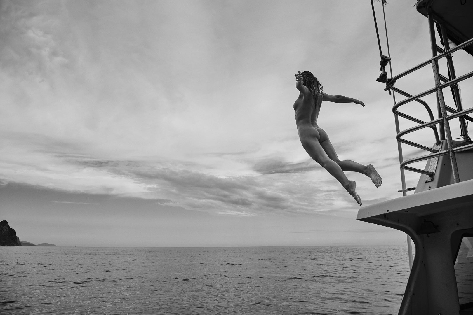 Naked girl jumping from boat by Stefan Rappo