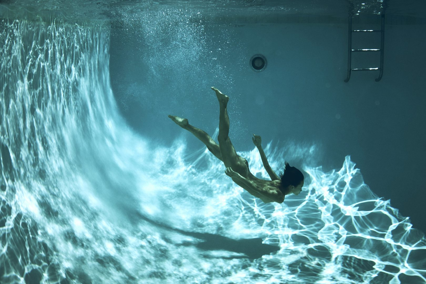 Naked girl diving in pool by Stefan Rappo