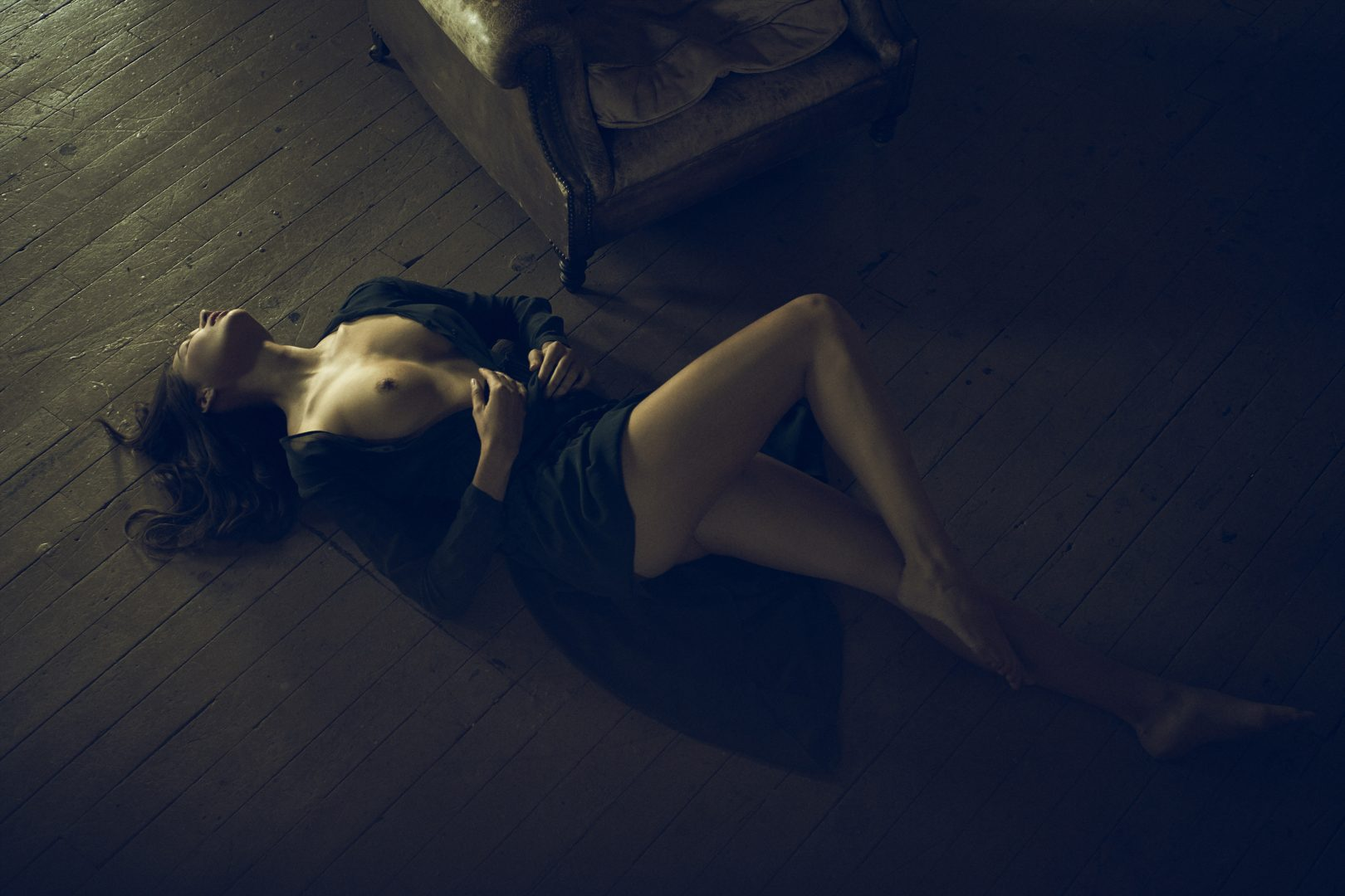 Girl lying on floor next to chair by Stefan Rappo