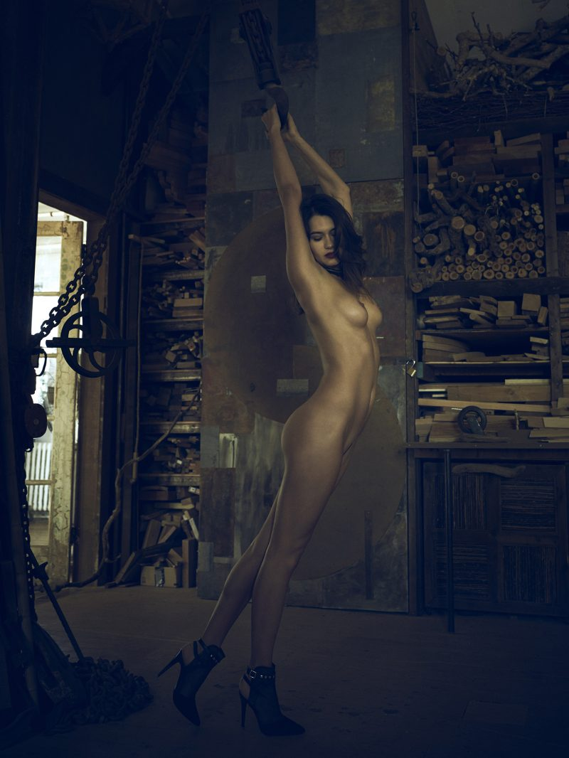 Naked girl hanging on chain by Stefan Rappo