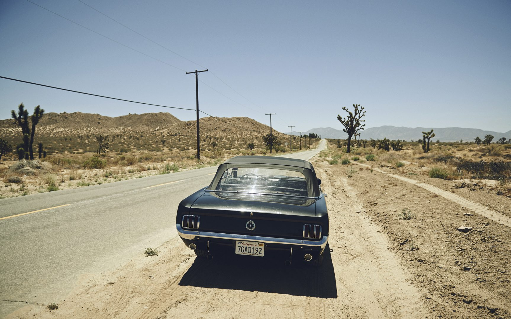 Ford Mustang parked in the desert by Stefan Rappo