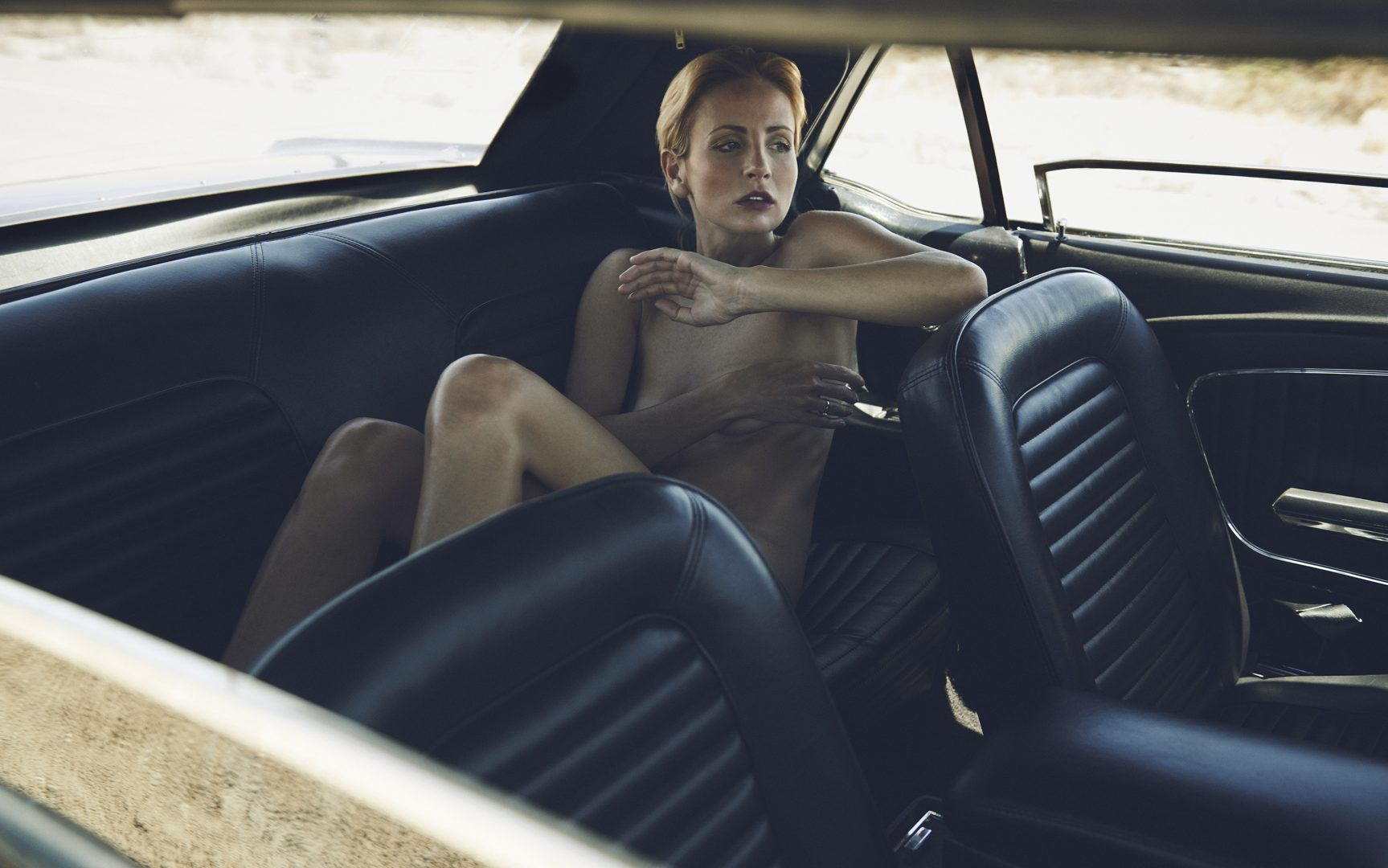 Girl lying naked in the back seat of a Ford Mustang in the desert by Stefan Rappo