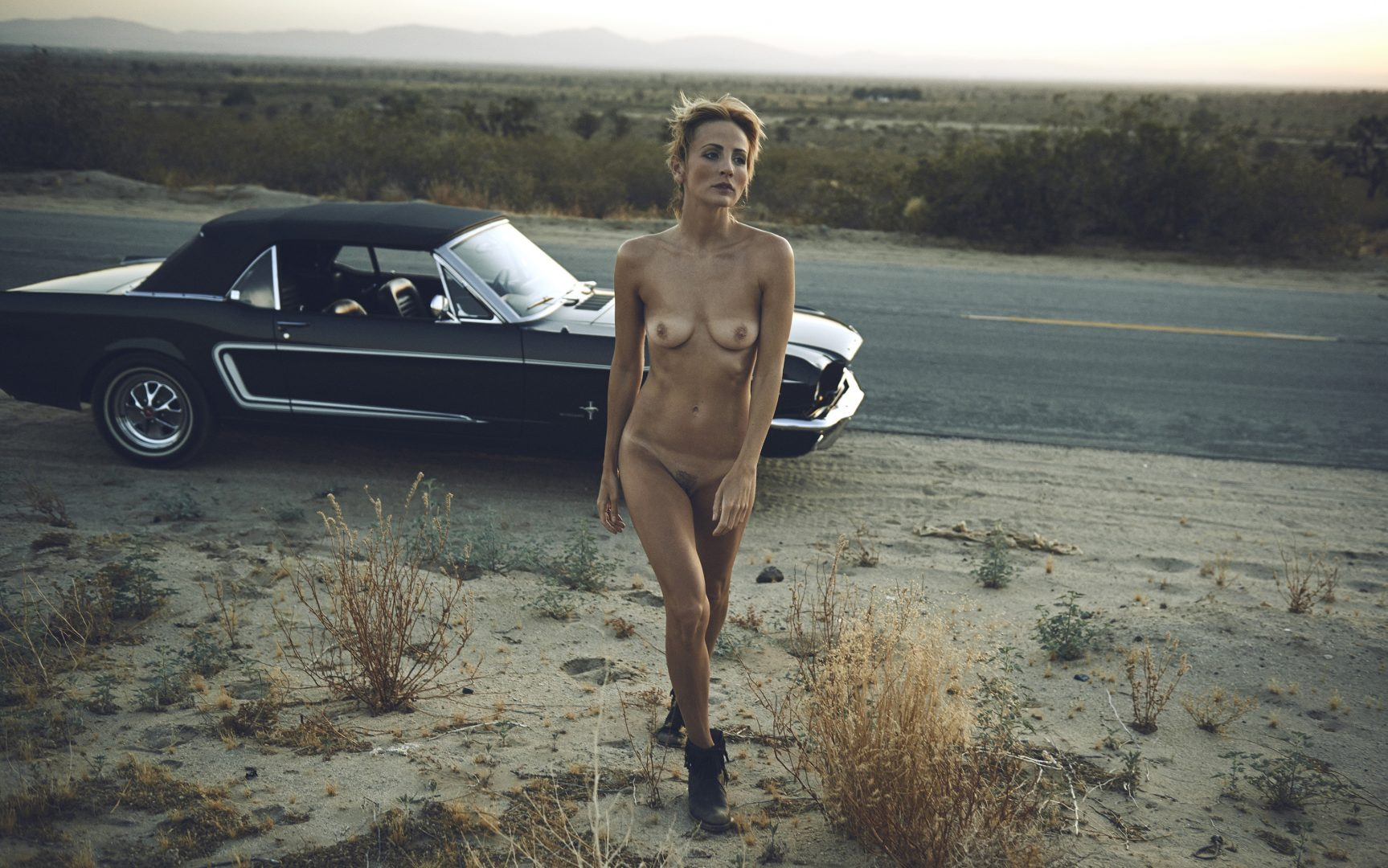 Naked girl walking away from a Ford Mustang in the desert after sunset by Stefan Rappo