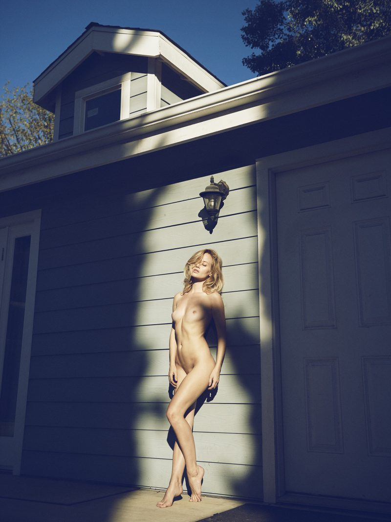 Naked girl leaning against a pool house by Stefan Rappo