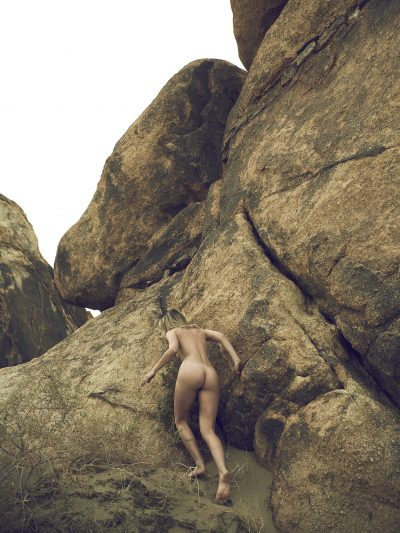 Naked girl climbing up rock in the desert by Stefan Rappo