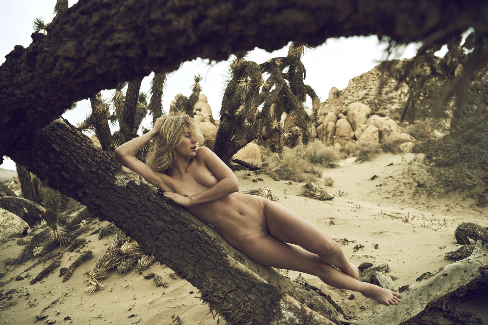 Naked girl lying on Joshua tree in the desert by Stefan Rappo