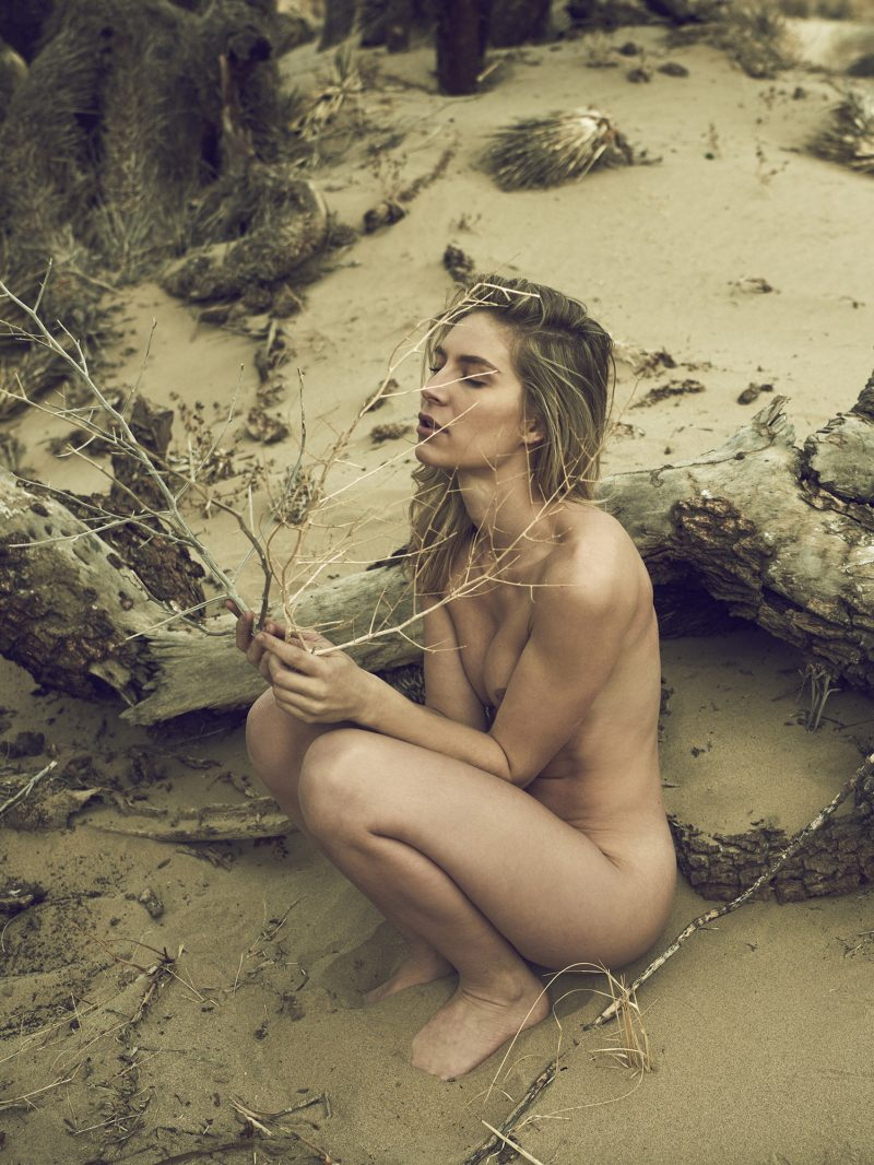 Naked girl playing with branch in the desert by Stefan Rappo
