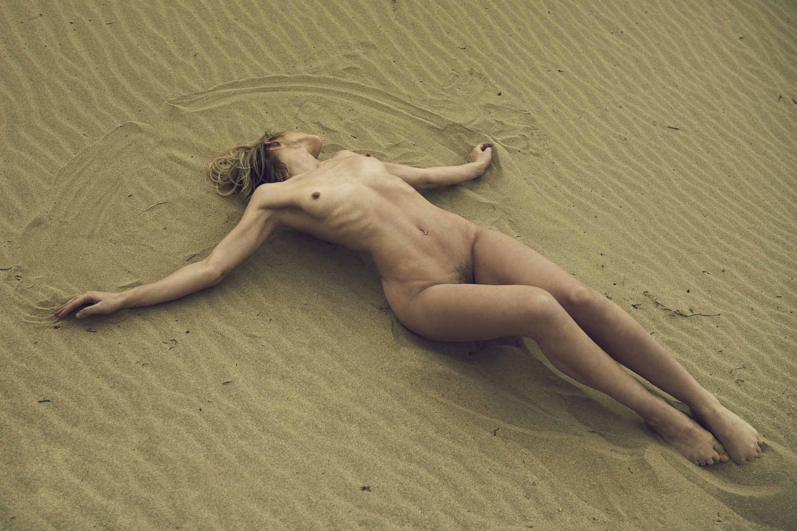 Naked girl lying on the floor in the desert by Stefan Rappo