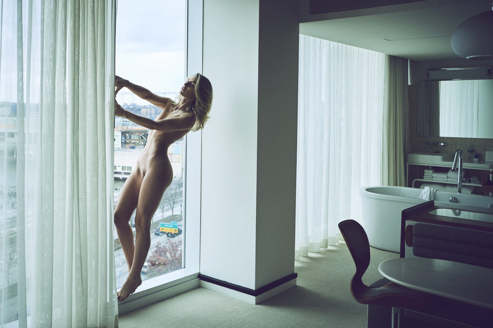 Naked girl standing at window in hotel room by Stefan Rappo