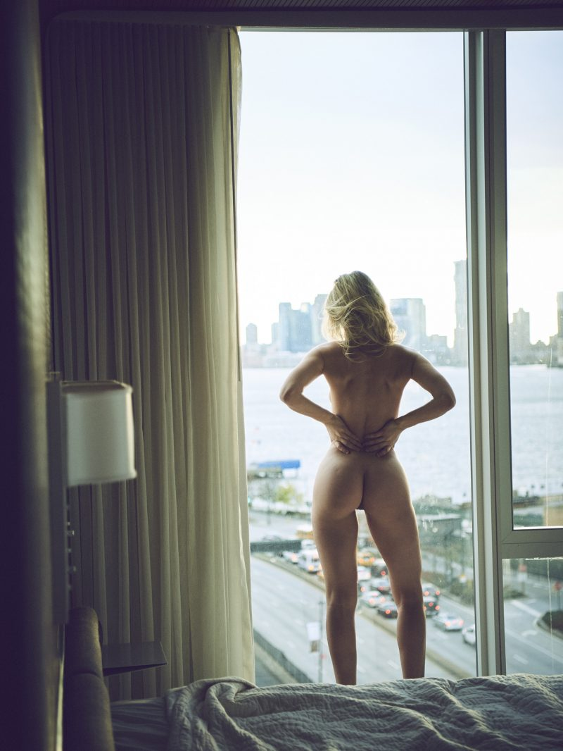Naked girl standing at the window in hotel room by Stefan Rappo