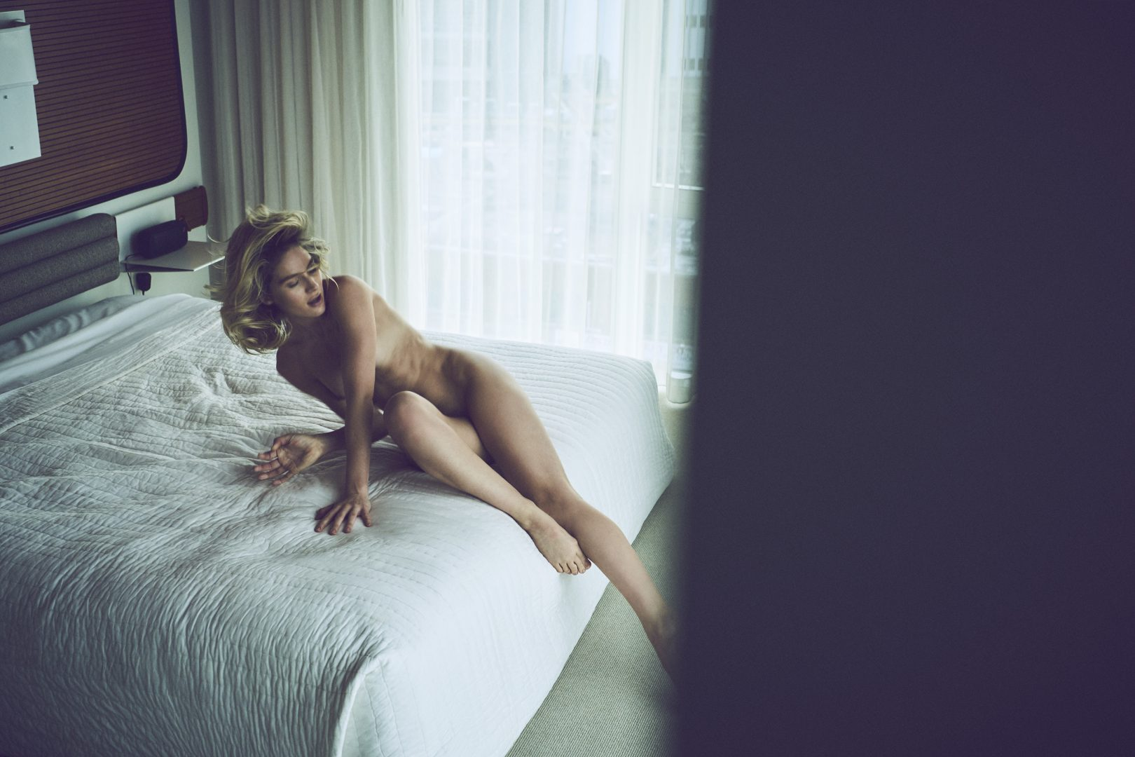 Naked girl jumping on bed in hotel room by Stefan Rappo