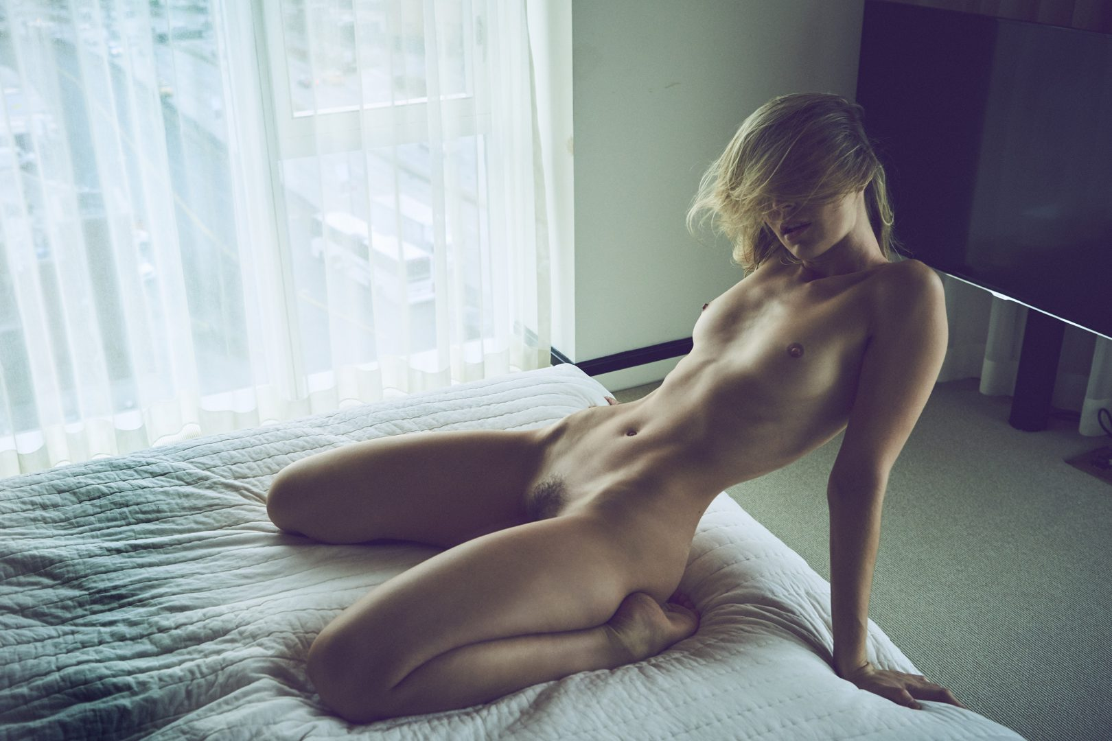 Naked girl sitting on bed in hotel room by Stefan Rappo