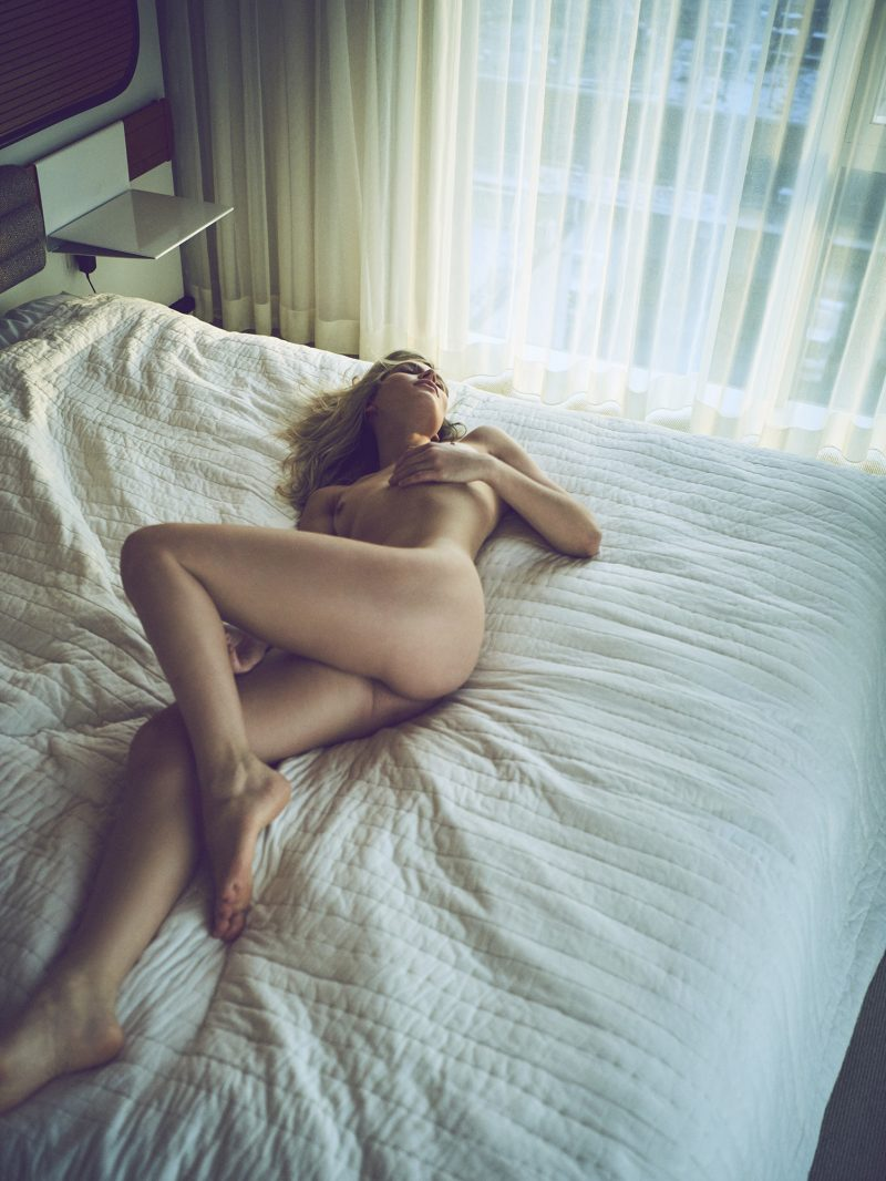 Naked girl lying on bed in hotel room by Stefan Rappo