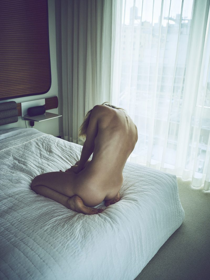 Naked girl on bed in hotel room by Stefan Rappo