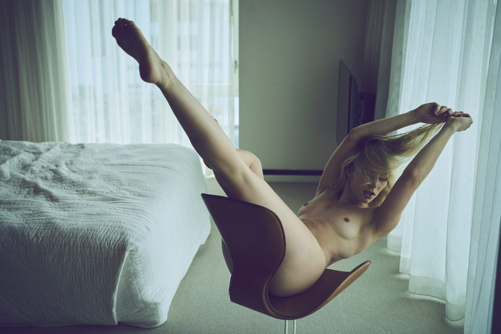 Naked girl on chair in hotel room by Stefan Rappo