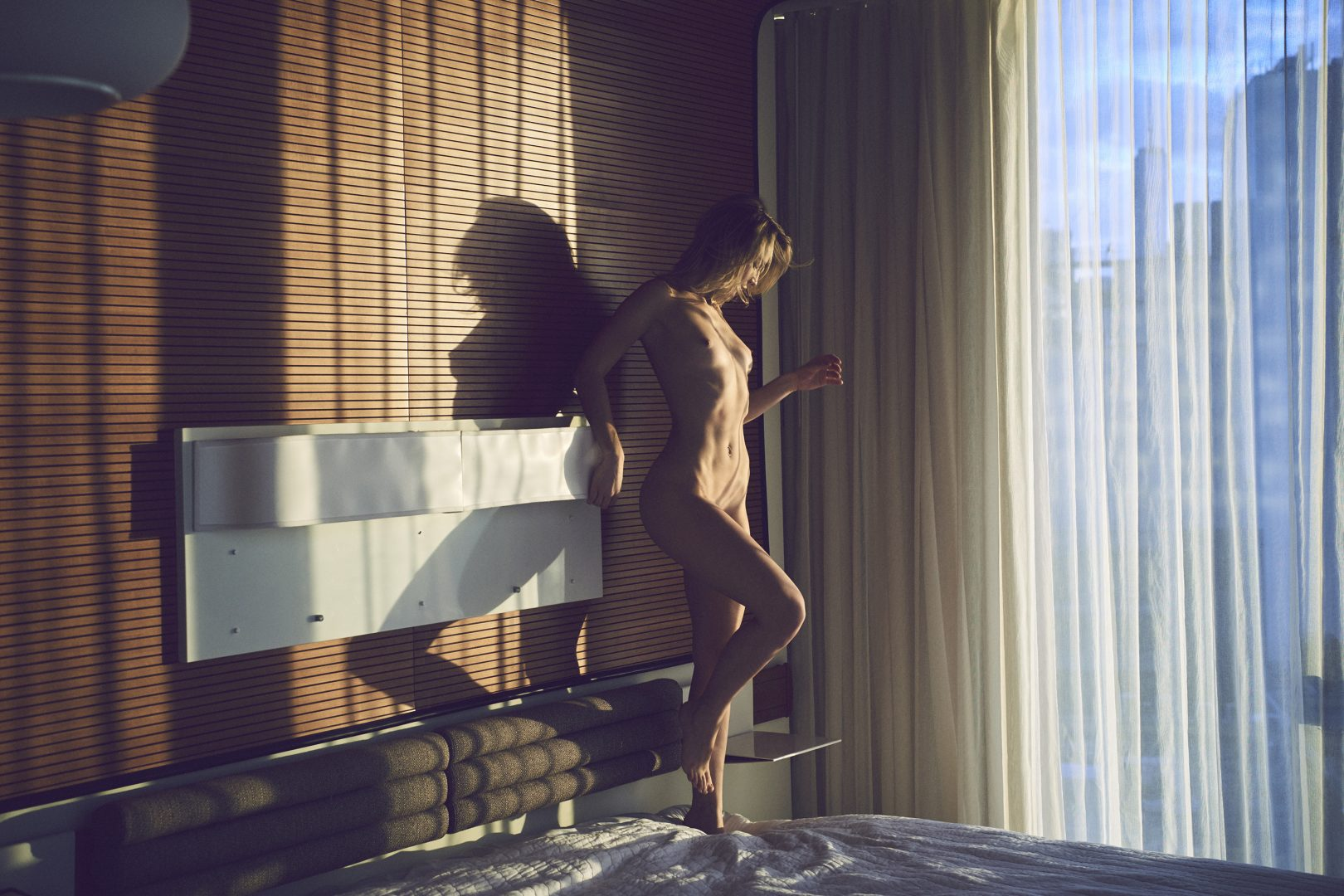 Naked girl standing on bed in hotel room by Stefan Rappo