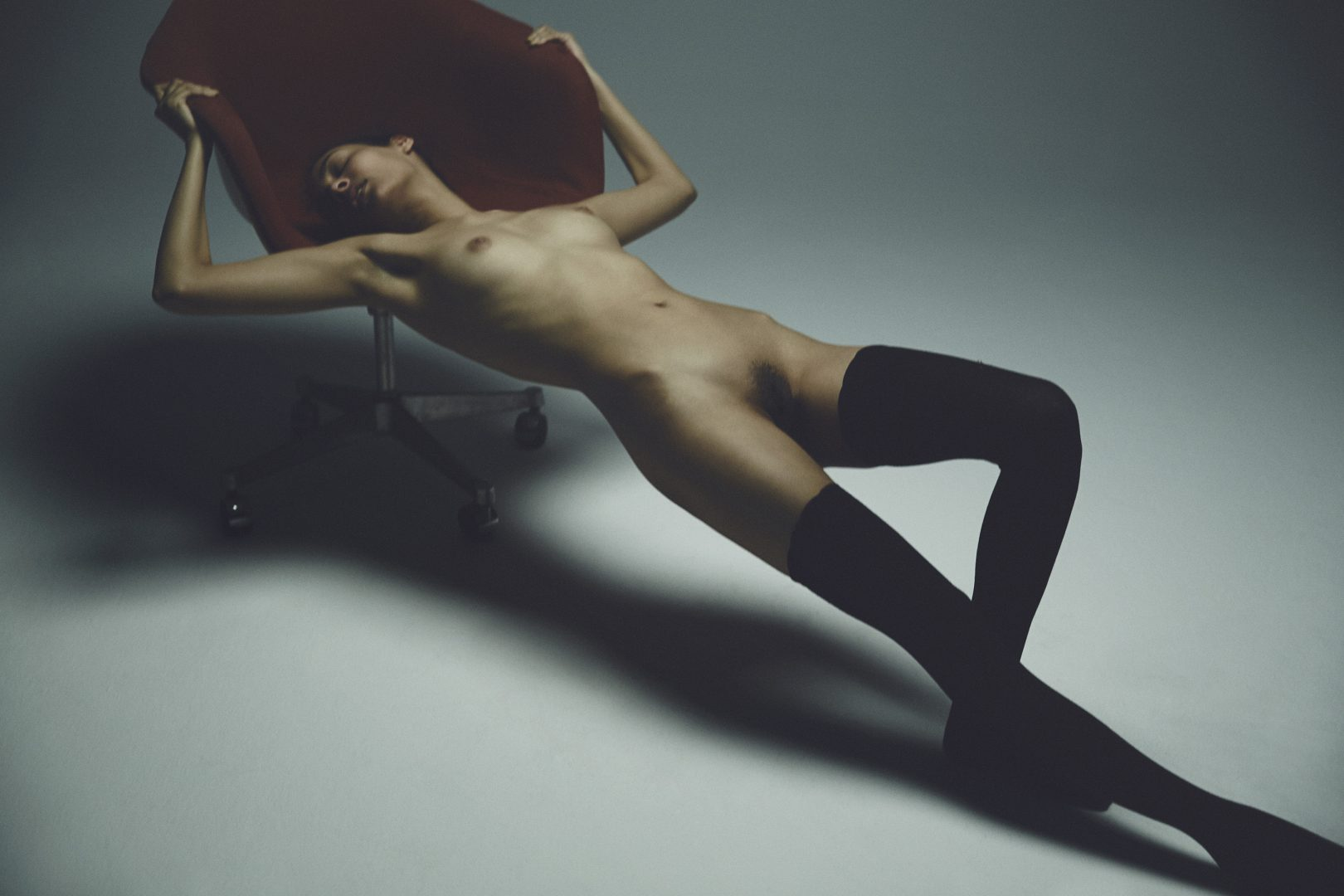 Girl lying naked on chair by Stefan Rappo