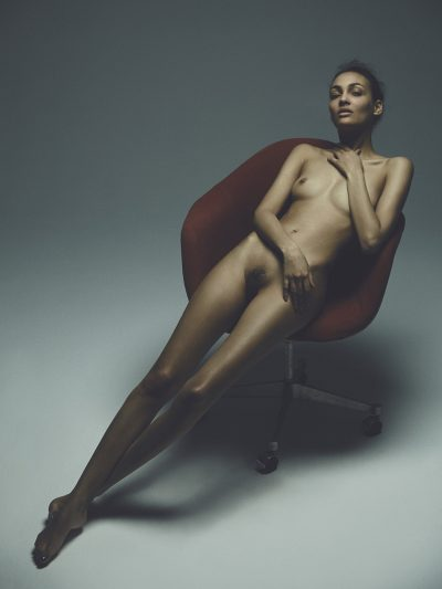 Girl sitting naked on chair by Stefan Rappo