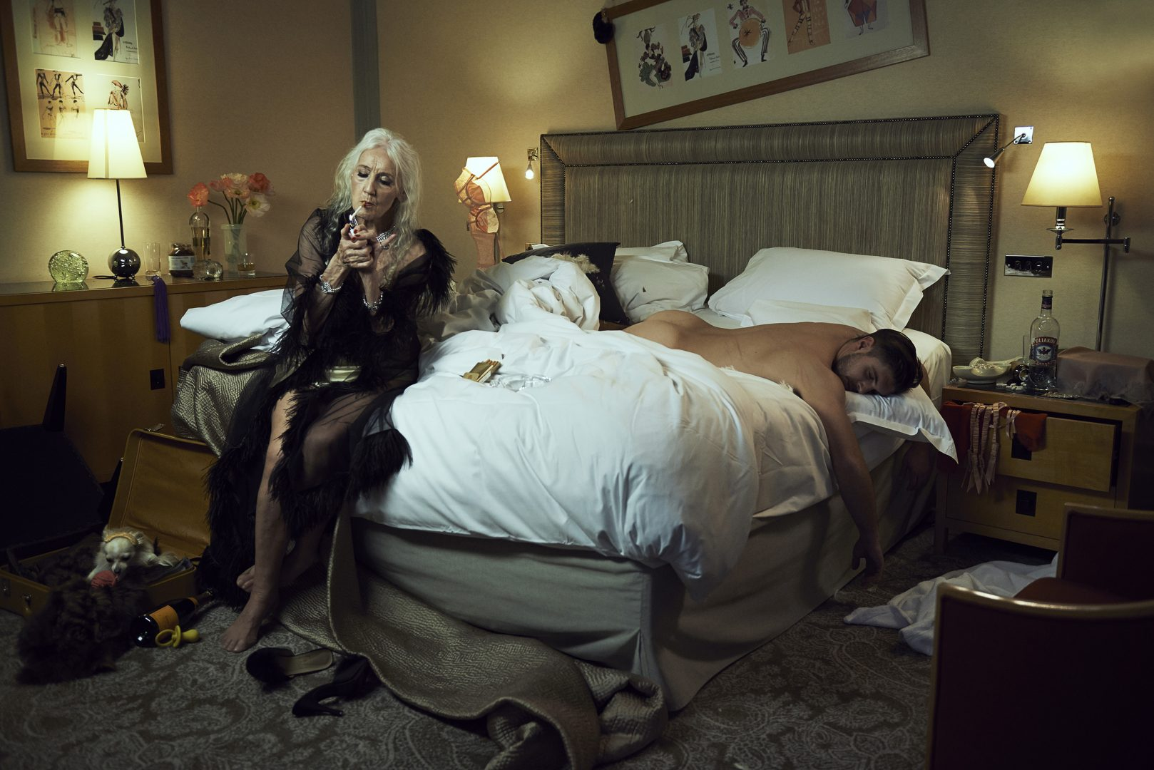 Old lady sitting on bed and smoking a cigaret beside a naked man in bed by Stefan Rappo