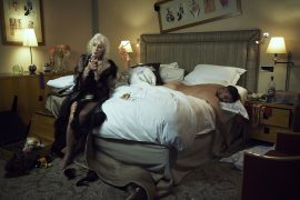 Thumbnail Old lady sitting on bed and smoking a cigaret beside a naked man in bed by Stefan Rappo