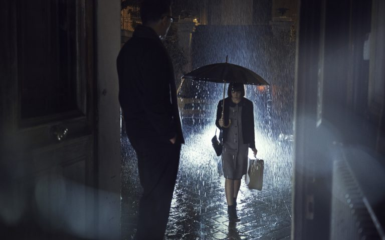 Girl walking to house under rain, man is waiting at her at the door by Stefan Rappo