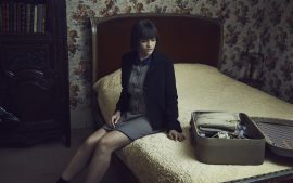 Thumbnail Girl sitting on bed and unpacking her suitcase by Stefan Rappo