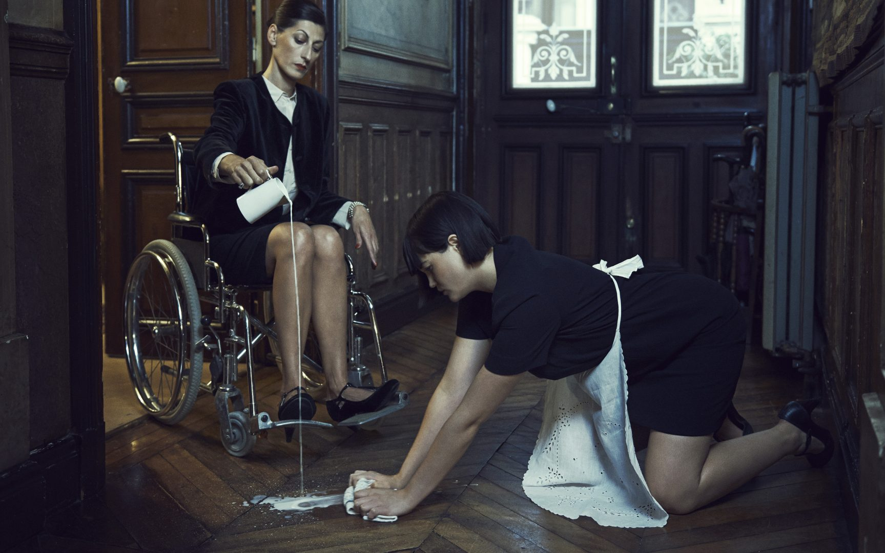 Women in wheel chair pour out milk on the floor, girl cleans it up by Stefan Rappo