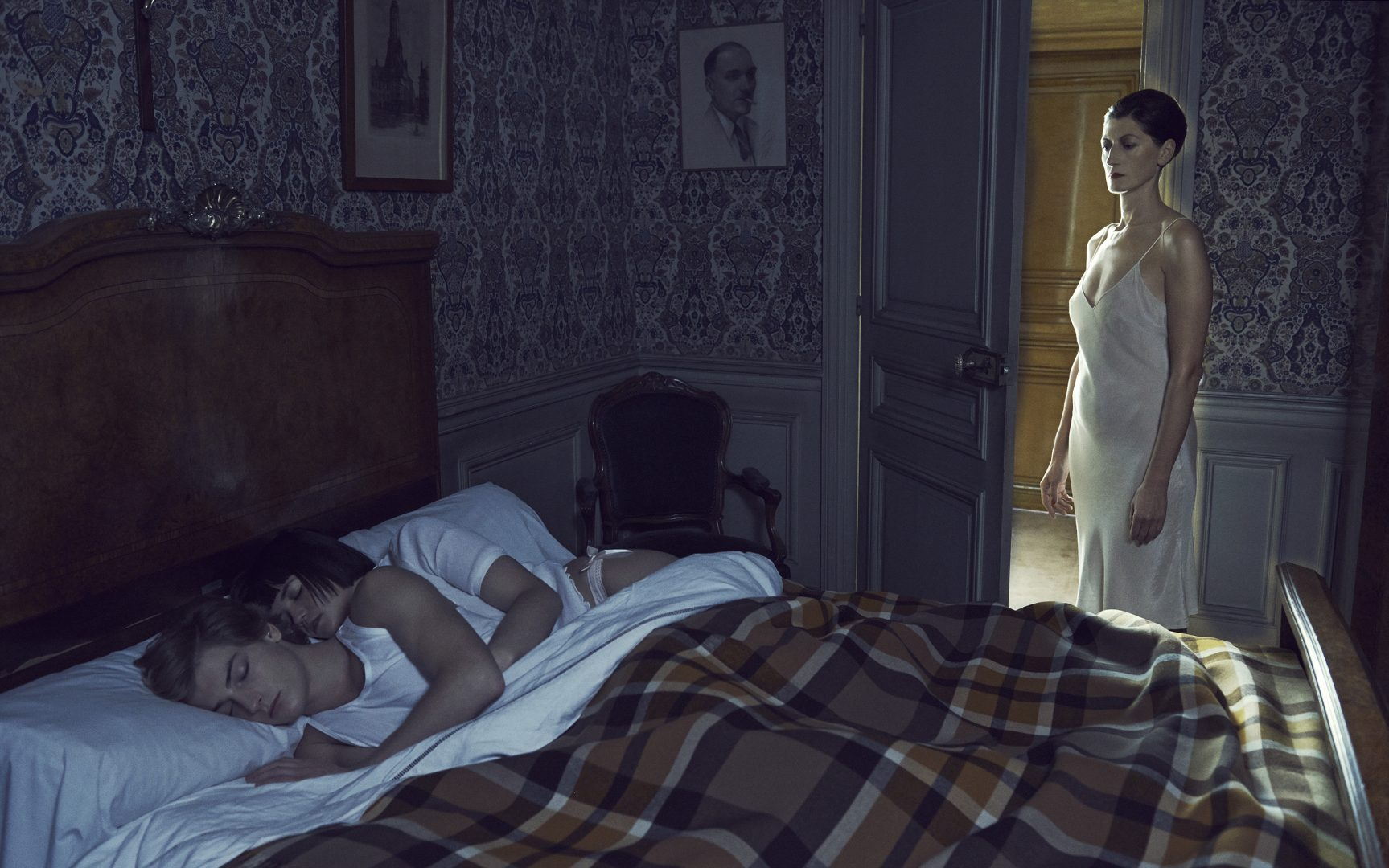 Couple of boy and girl sleeping in bed and being watched by women by Stefan Rappo