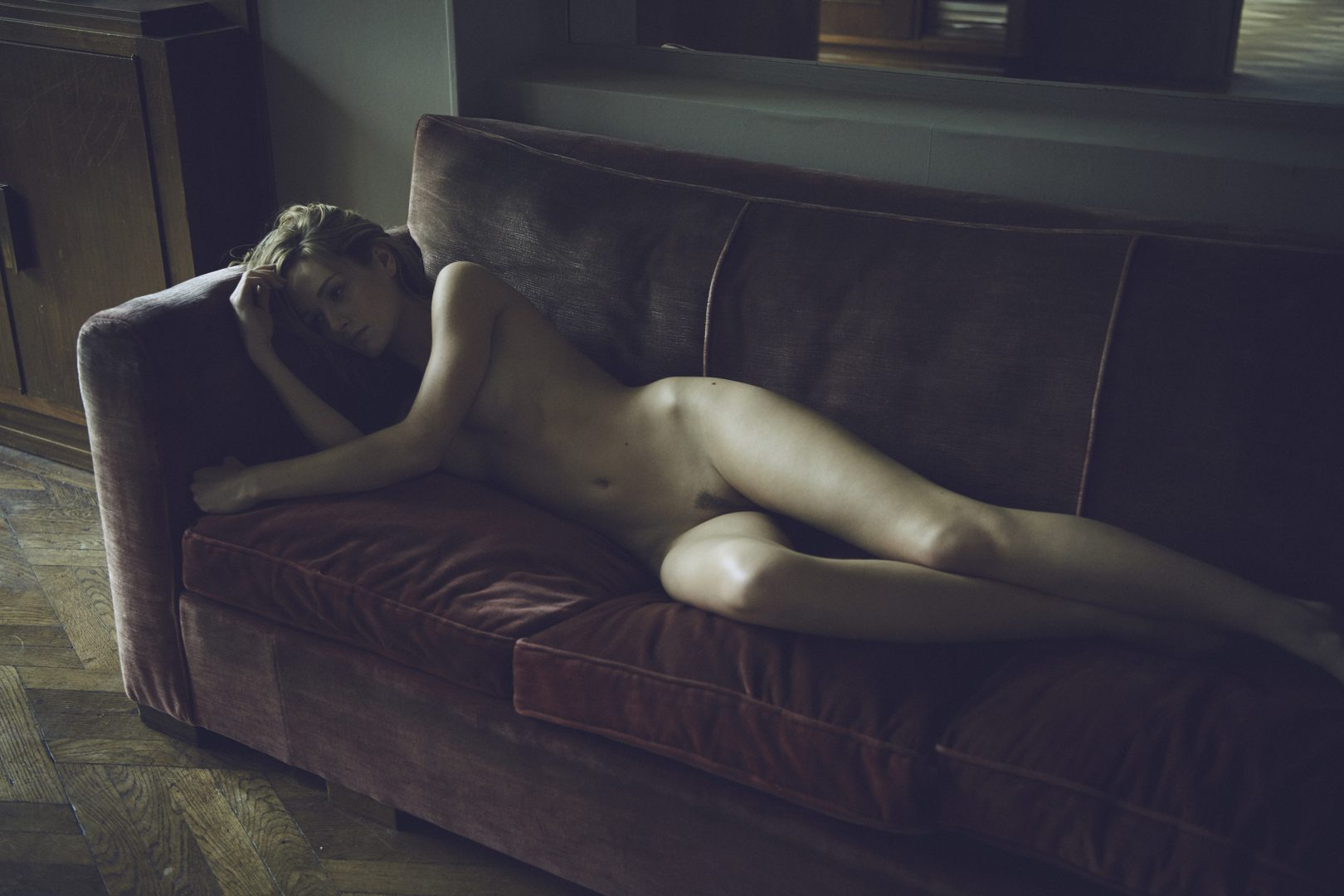 naked girl lying on sofa by Stefan Rappo