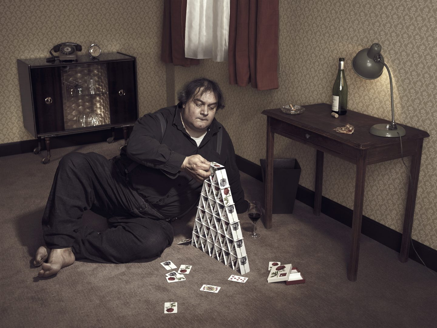 Man on floor is building a card house in room 42 by Stefan Rappo