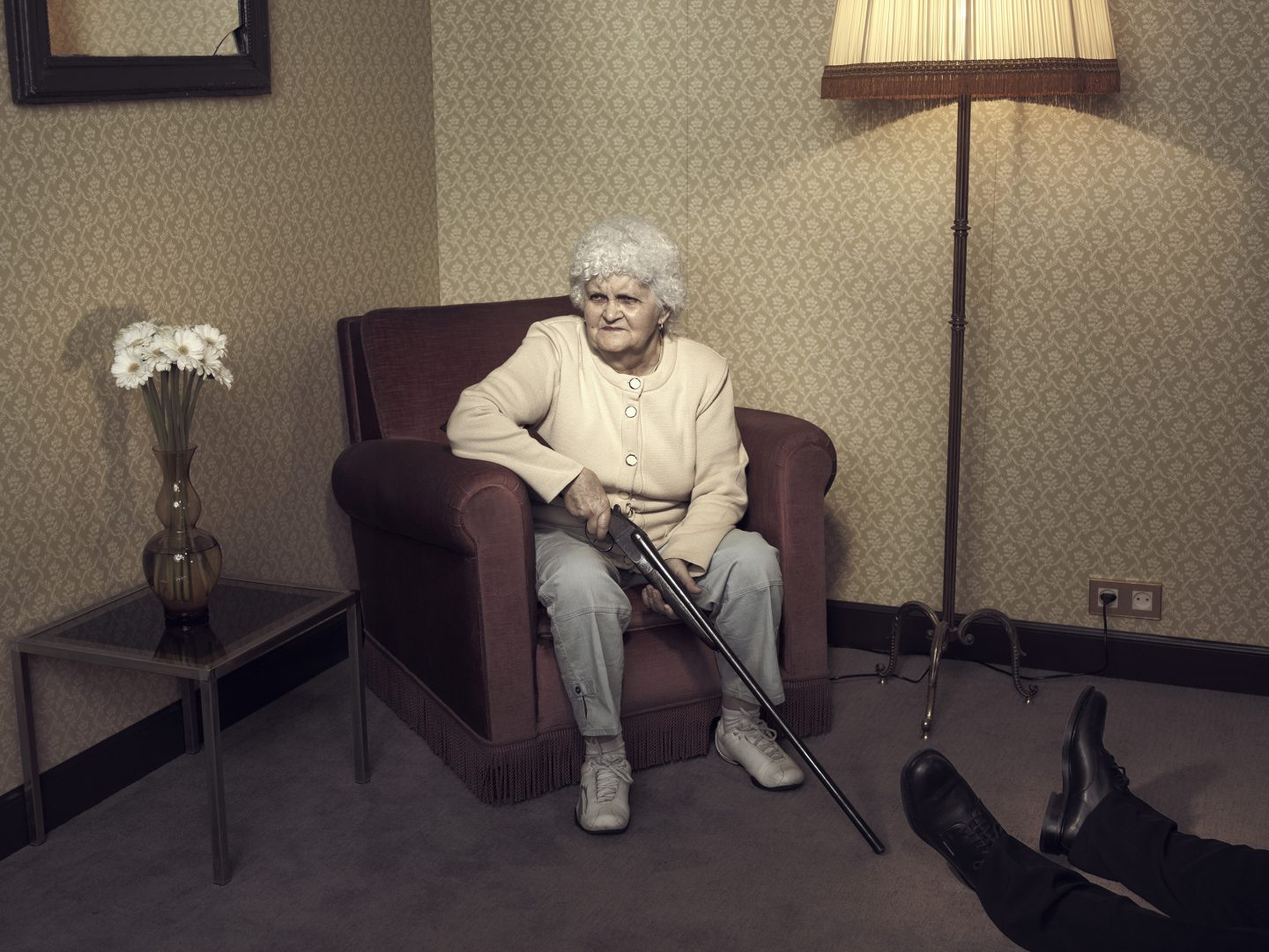 Old lady sitting in chair with gun in room 42 by Stefan Rappo