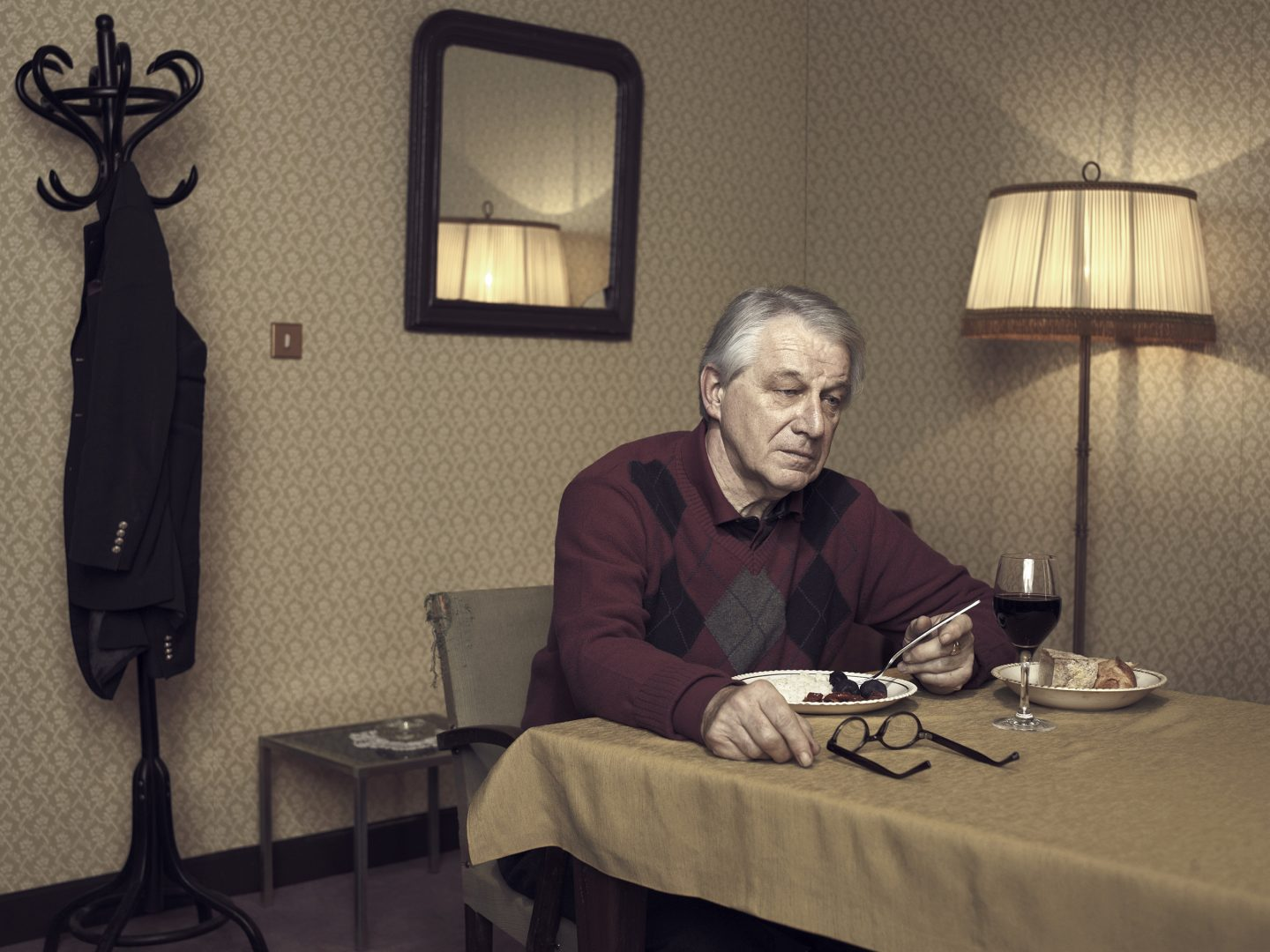 Lonely man having diner alone in room 42 by Stefan Rappo