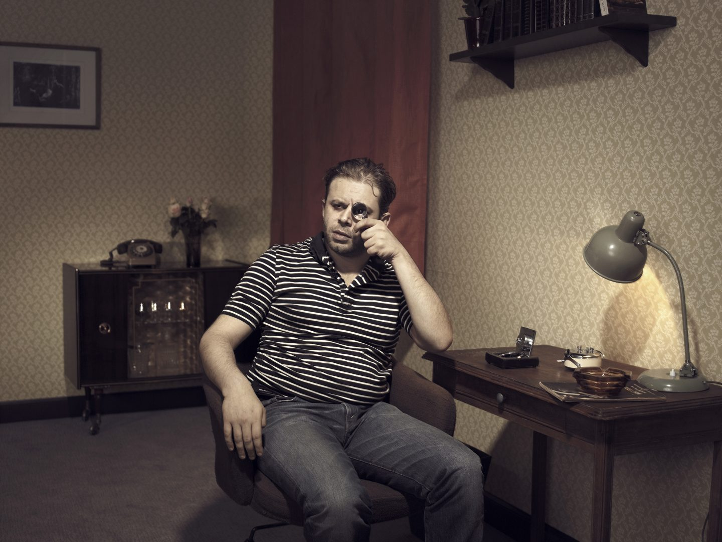 Man looking trough a magnifying glass in room 42 by Stefan Rappo
