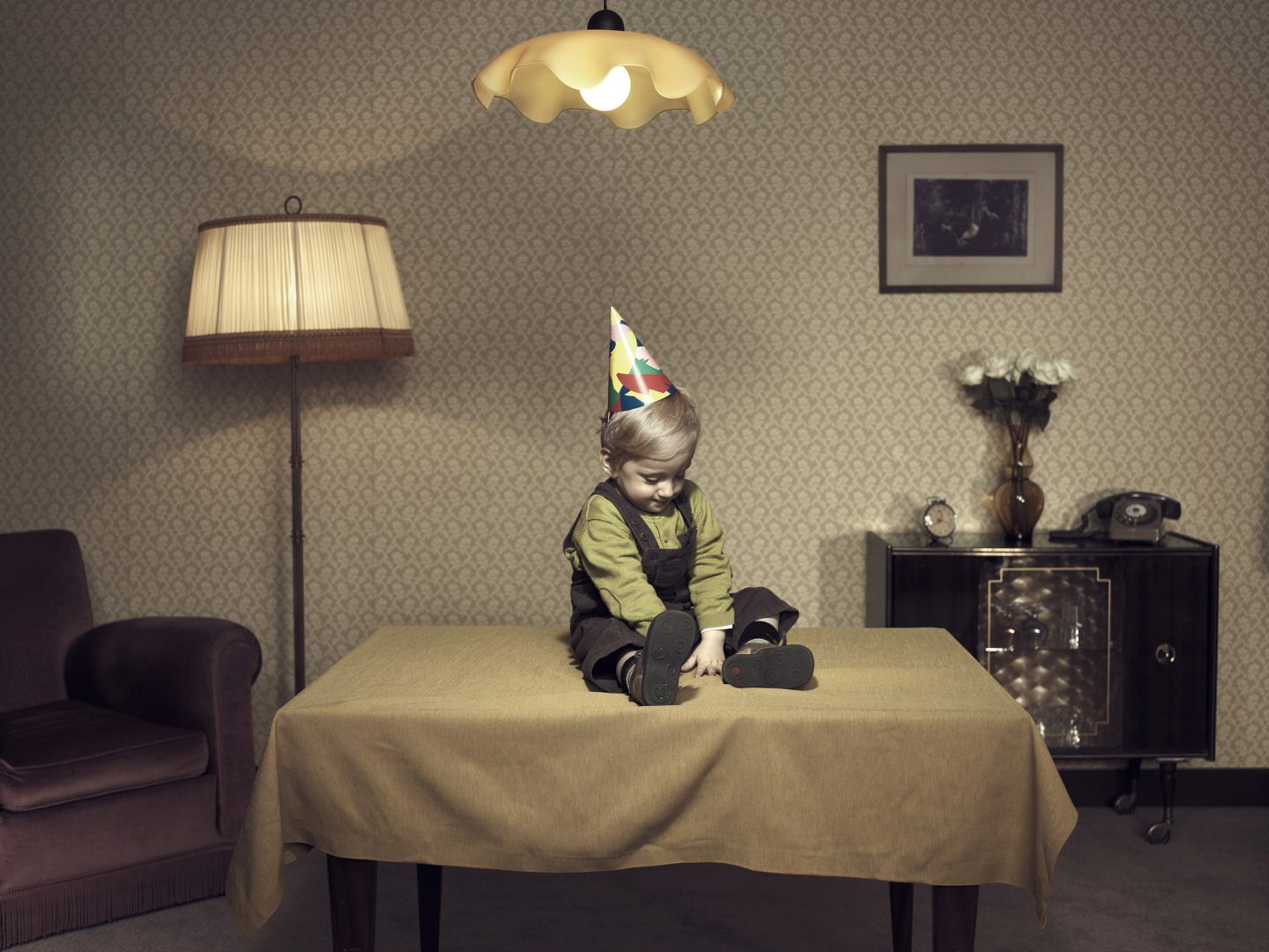 Kid sitting on table in room 42 by Stefan Rappo