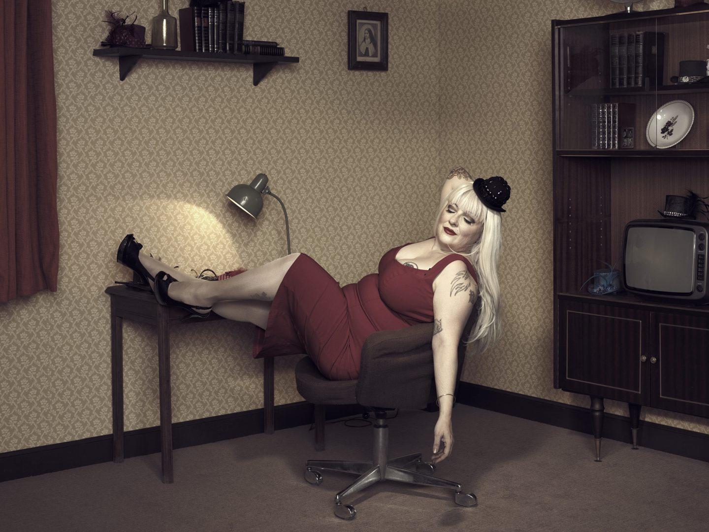 Woman in red dress sitting on chair in room 42 by Stefan Rappo
