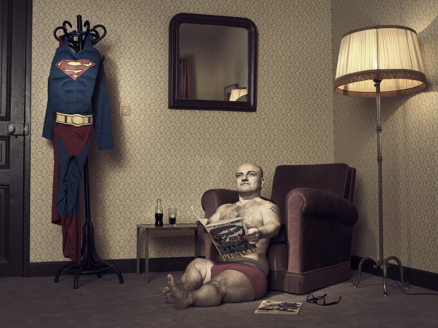 Dwarf sitting on floor with super man comic in room 42 by Stefan Rappo