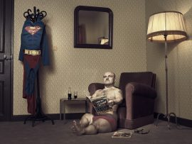 Thumbnail Dwarf sitting on floor with super man comic in room 42 by Stefan Rappo