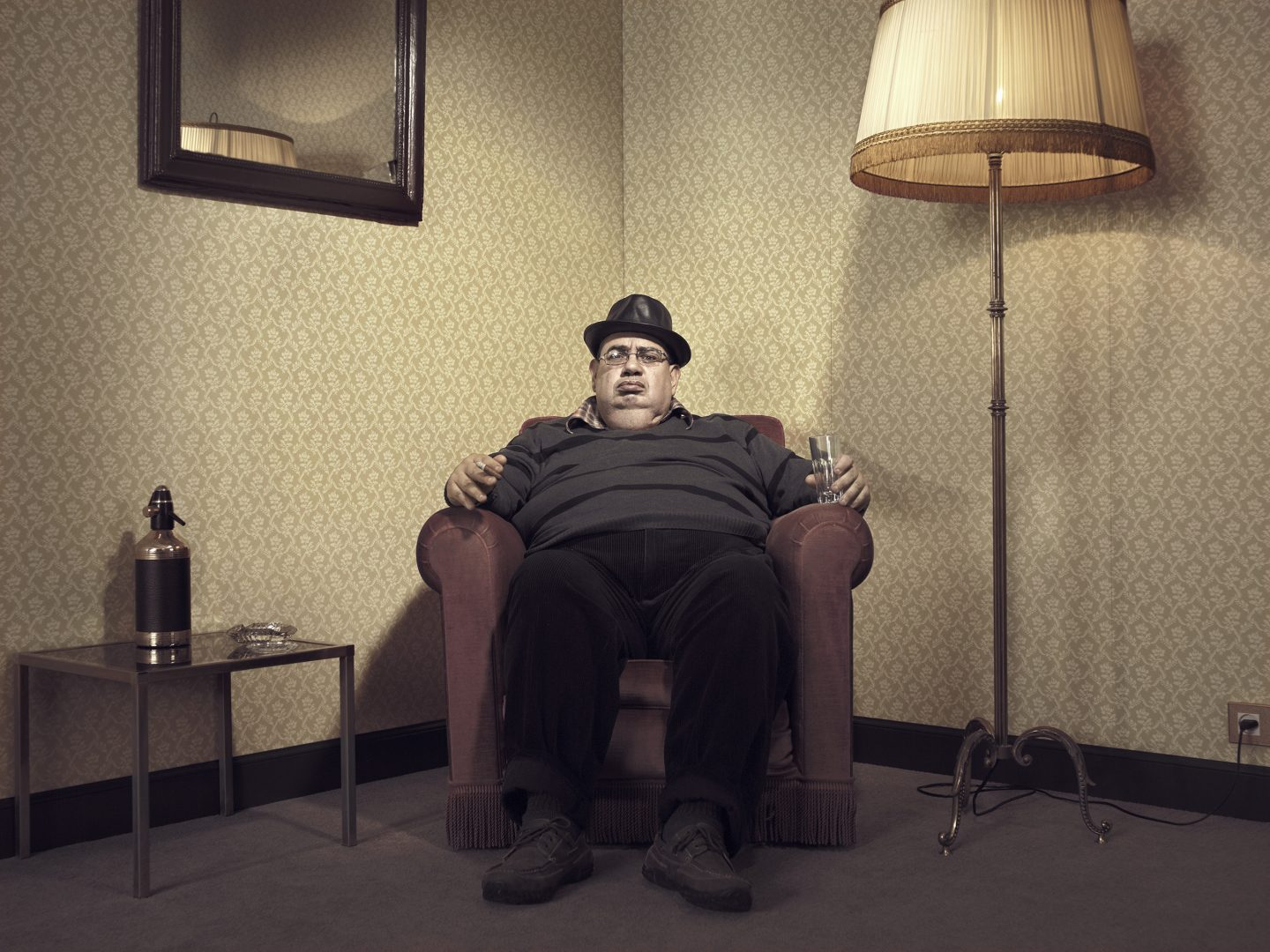Man with hat sitting in armchair in room 42 by Stefan Rappo