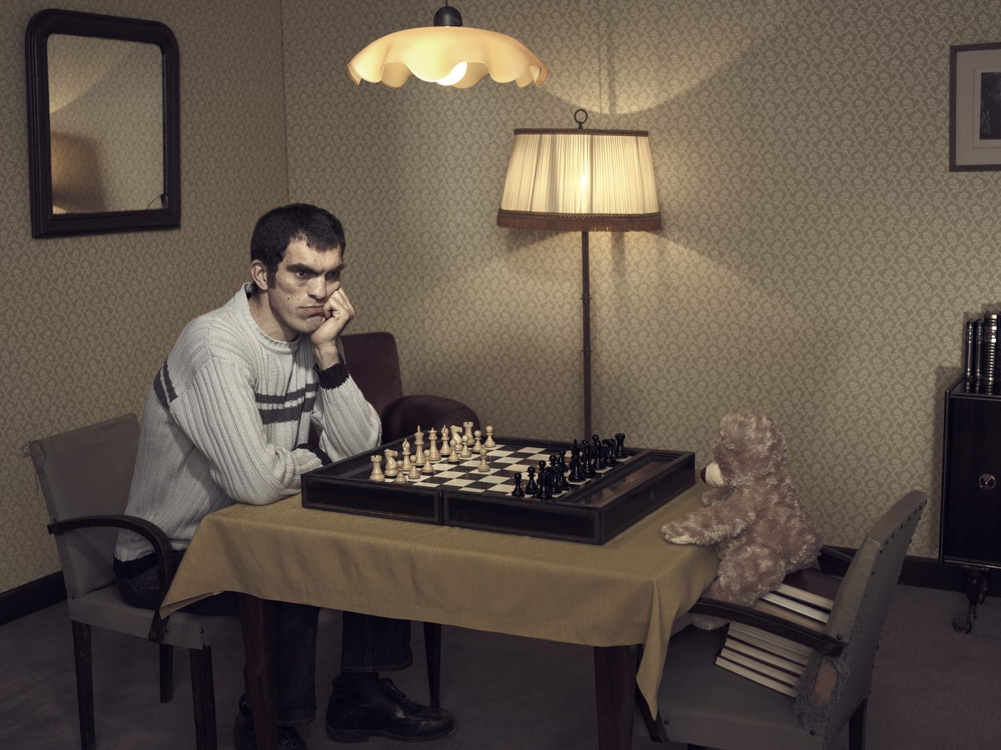Man playing chess with teddy in room 42 by Stefan Rappo