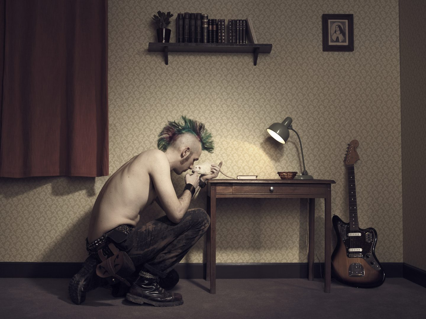 Punk playing with his rat in room 42 by Stefan Rappo